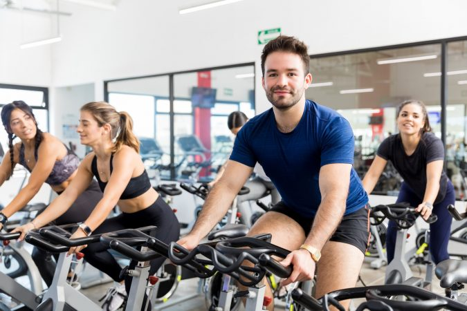 A spin class with members sat on the spin bikes