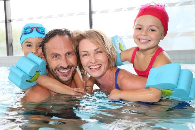 A family in a swimming pool, with children sat on their parents backs and wearing arm bands